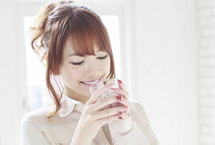 """一个女人喝""""黄金菊芋錠""""的形象"""